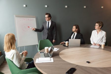 confident-speaker-business-coach-gives-presentation-team-with-flipchart_1163-4782